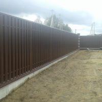 Забор из металлического штакетника и профлиста на ленточном фундаменте с кирпичными столбами